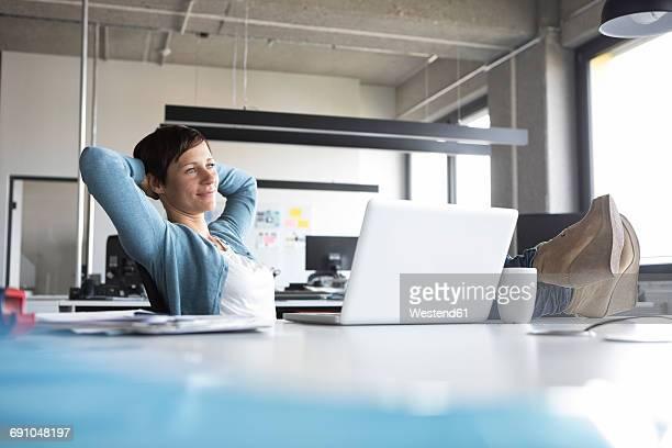 businesswoman in office at desk relaxing - hände hinter dem kopf stock-fotos und bilder
