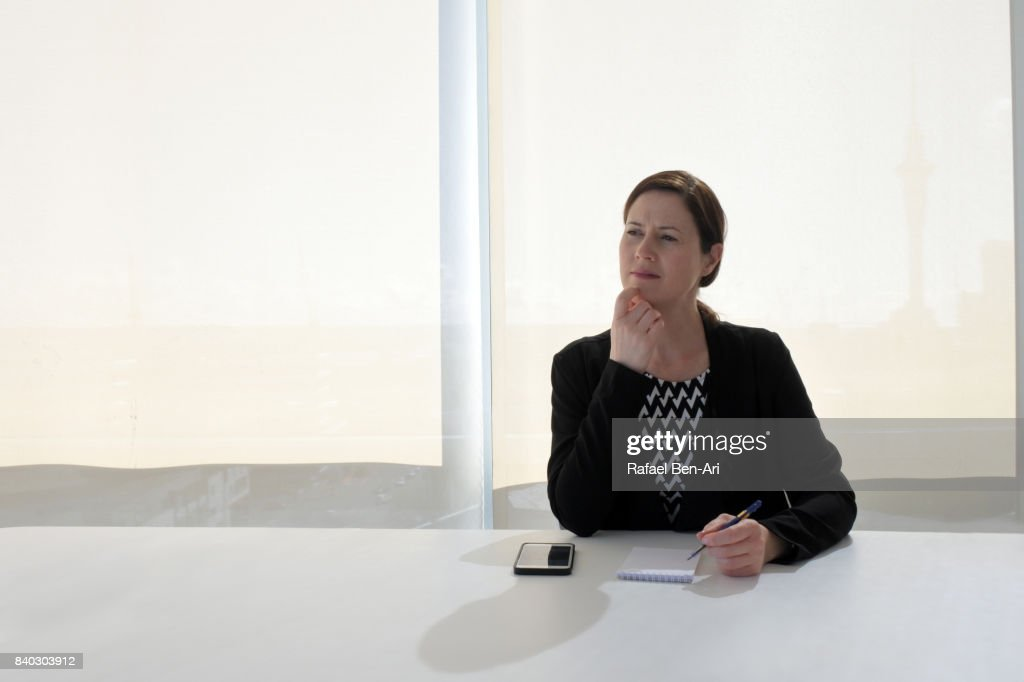 Businesswoman in office behind a desk thinking about new project : Stock Photo