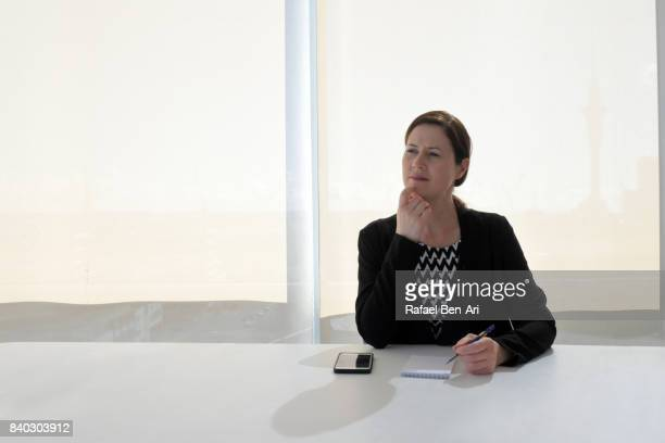Businesswoman in office behind a desk thinking about new project