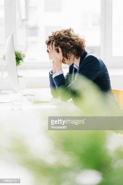 Businesswoman in office burying head in hands