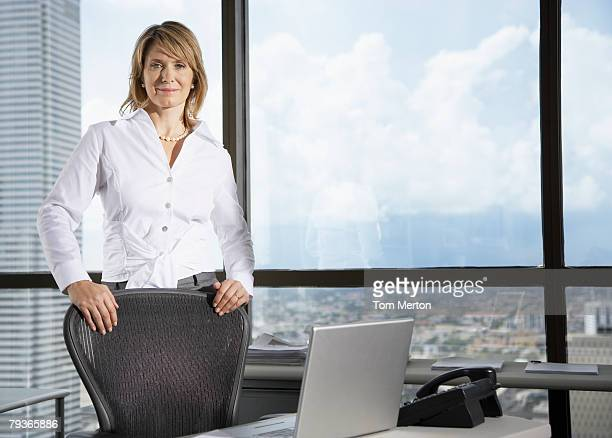 Businesswoman in office by large windows looking at camera