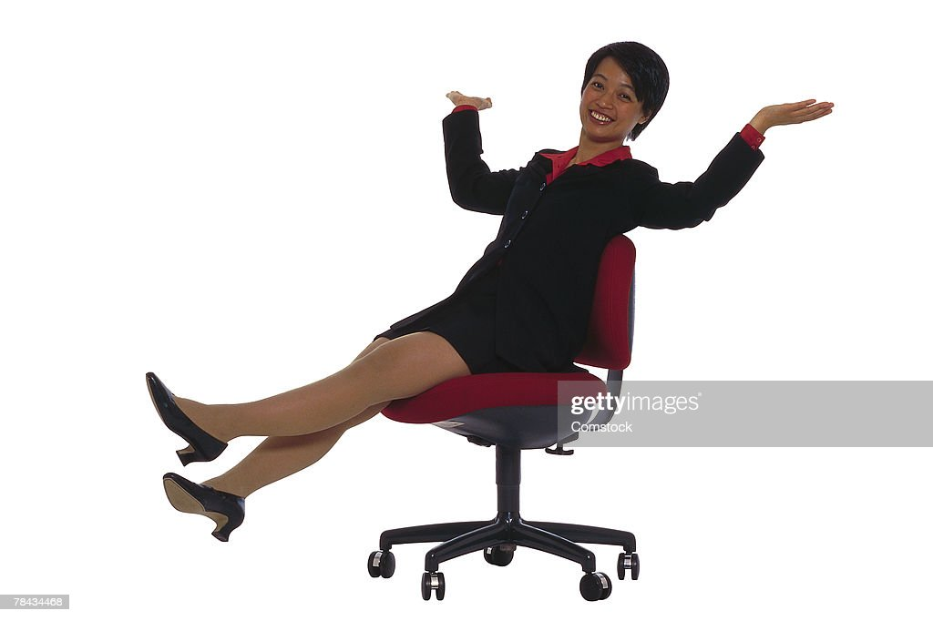 Businesswoman in office chair rolling across floor : Stockfoto