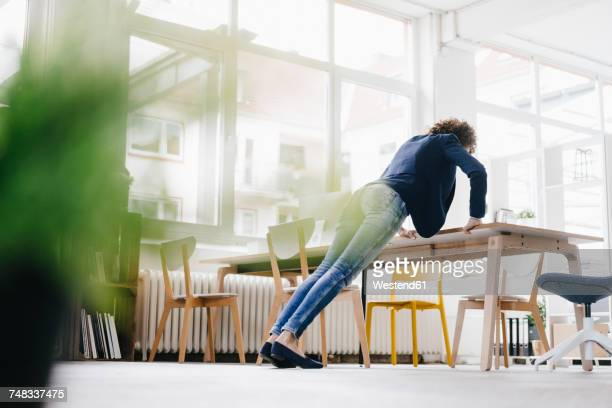 businesswoman in office doing push ups on desk - pauze nemen stockfoto's en -beelden