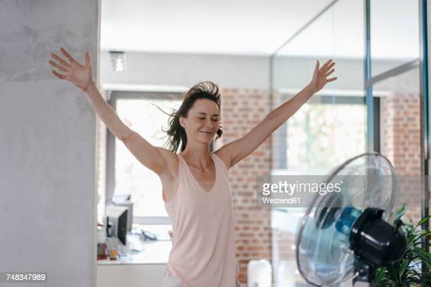 businesswoman in office enjoying breeze from a fan - calientes fotografías e imágenes de stock