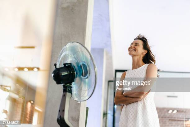 businesswoman in office enjoying breeze from a fan - hot older women stock pictures, royalty-free photos & images