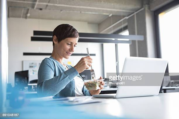 businesswoman in office having lunch break - almoço imagens e fotografias de stock
