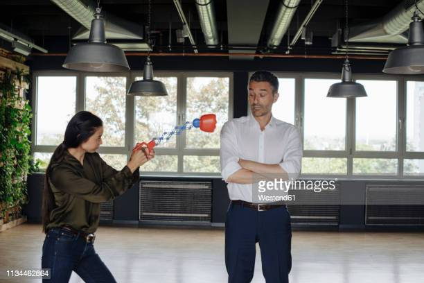 businesswoman in office hitting businessman with boxing toy - funny boxing stock photos and pictures