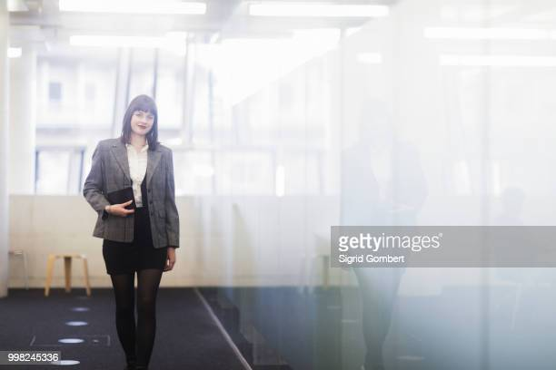 businesswoman in office holding digital tablet - sigrid gombert stockfoto's en -beelden