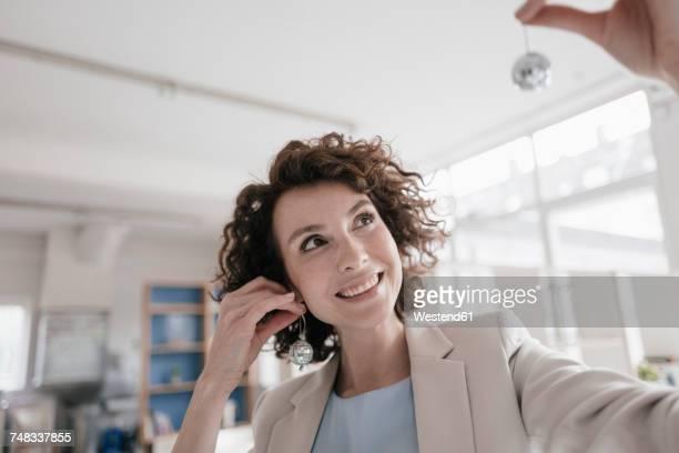 businesswoman in office holding disco balls on her ears - ohrring stock-fotos und bilder