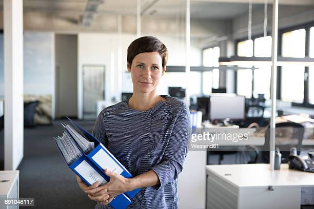Businesswoman in office holding folders