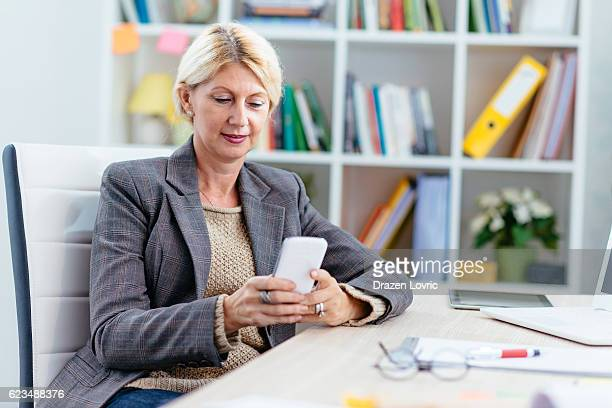 Businesswoman in office holding phone and texting