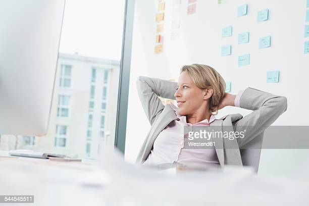 Businesswoman in office leaning back