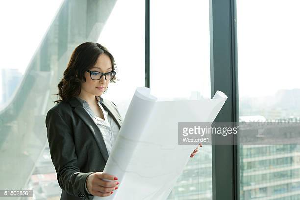 Businesswoman in office looking at blueprint