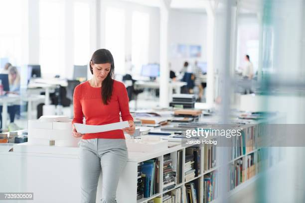 businesswoman in office looking at blueprints - focus on background stock pictures, royalty-free photos & images