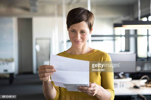 Businesswoman in office looking at paper