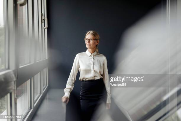 businesswoman in office looking out of window - dreiviertelansicht stock-fotos und bilder