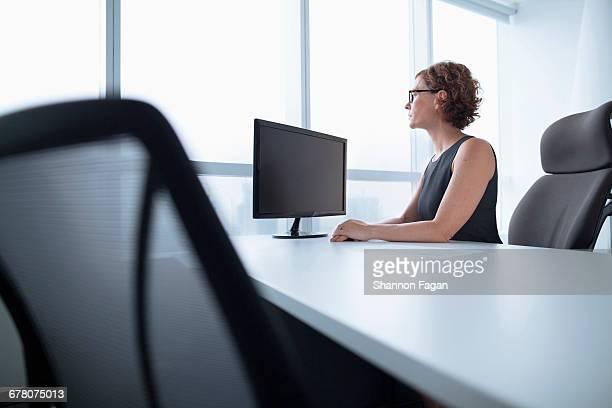businesswoman in office looking out of window - solo una donna matura foto e immagini stock