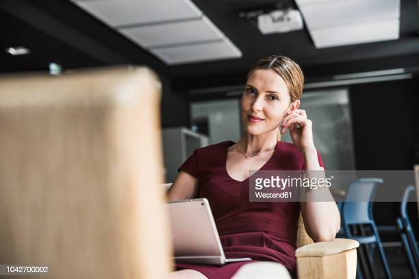 Businesswoman in office lounge wearing burgundy dress using laptop