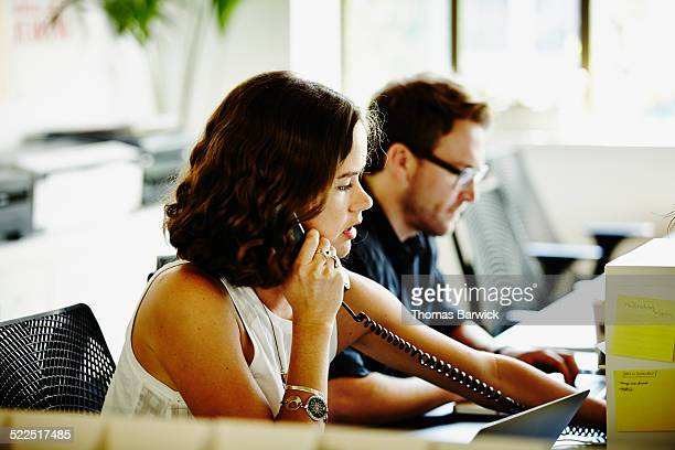 businesswoman in office making phone call - leanintogether stock pictures, royalty-free photos & images