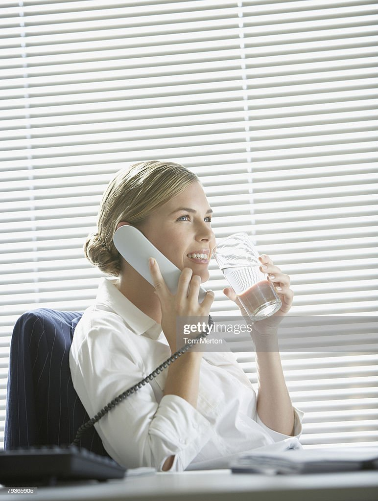 Businesswoman in office on telephone with water by large windows : Stock Photo