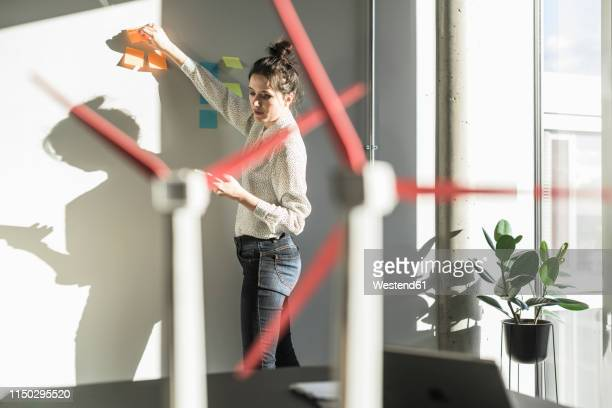 businesswoman in office putting sticky notes on wall with wind turbine models on desk - putting stock photos and pictures