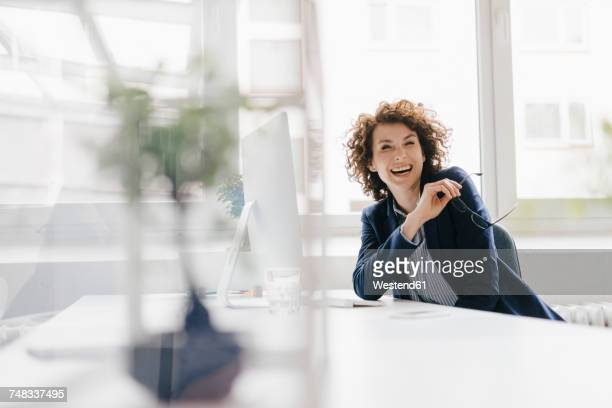 businesswoman in office sitting at desk, laughing - vitalität stock-fotos und bilder
