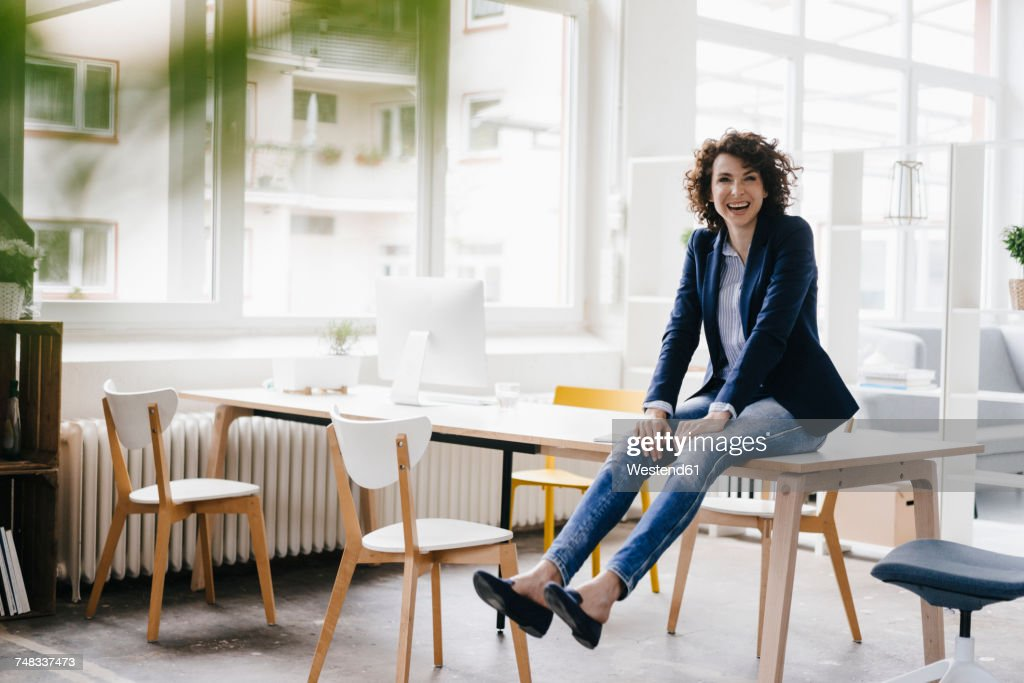 Businesswoman in office sitting on desk, having fun : Stock Photo