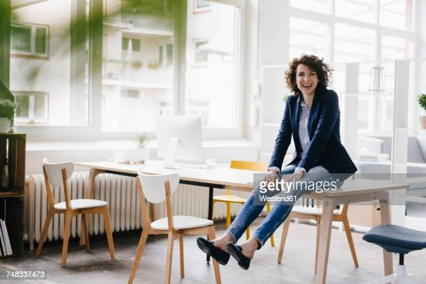 Businesswoman in office sitting on desk, having fun