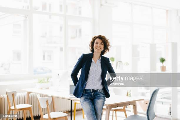 businesswoman in office sitting on desk, looking confident - mid adult stock-fotos und bilder