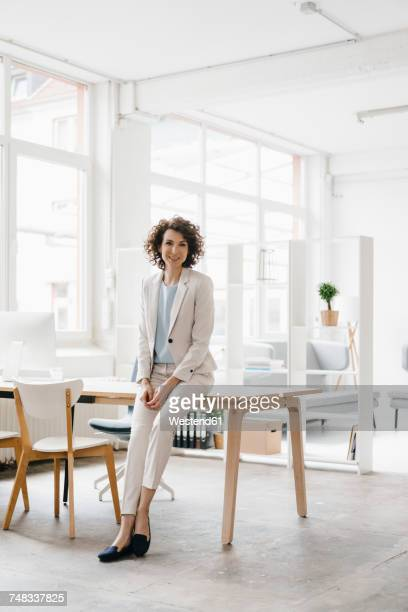 businesswoman in office sitting on desk, looking confident - businesswear stock pictures, royalty-free photos & images
