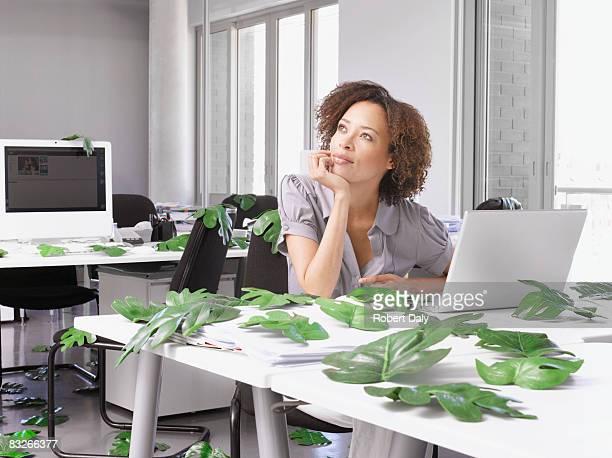 Geschäftsfrau in Büro umgeben von Blätter