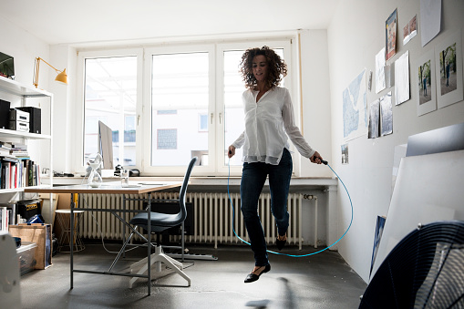Businesswoman in office, training with skipping rope - gettyimageskorea