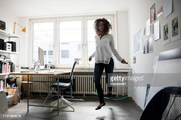 businesswoman in office, training with skipping rope - skipping rope stock pictures, royalty-free photos & images