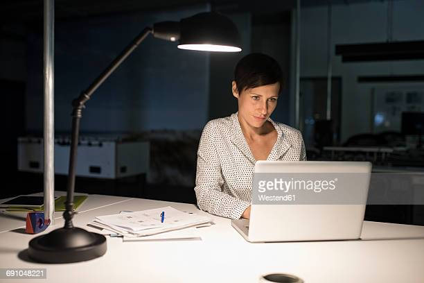Businesswoman in office using laptop in the dark