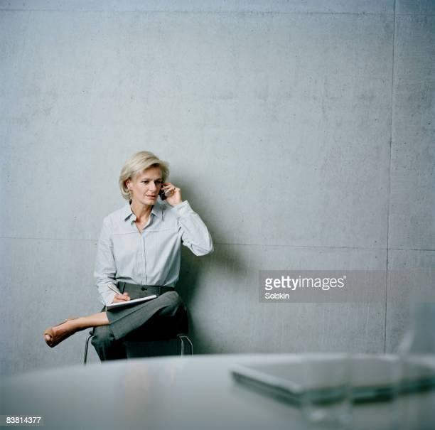 businesswoman in office,  using mobile phone - cabelo curto comprimento de cabelo imagens e fotografias de stock