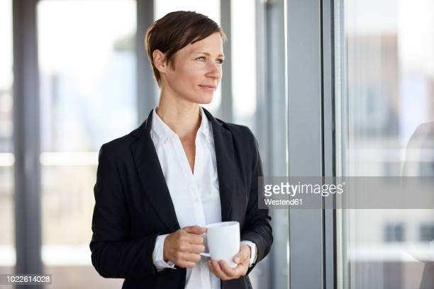 businesswoman in office with cup of coffee looking out of window - seitenblick stock-fotos und bilder