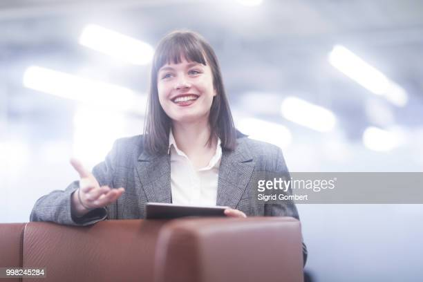 businesswoman in office with digital tablet smiling - sigrid gombert stockfoto's en -beelden