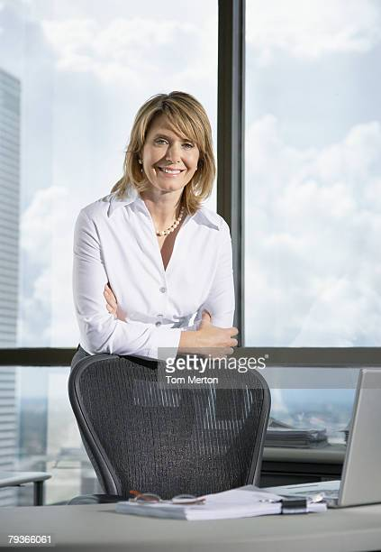 Businesswoman in office with laptop by large windows
