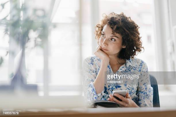 businesswoman in office with smartphone and diary, looking worried - 思索にふける ストックフォトと画像