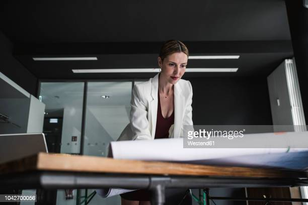 businesswoman in office working on plan at desk - 女性建築家 ストックフォトと画像