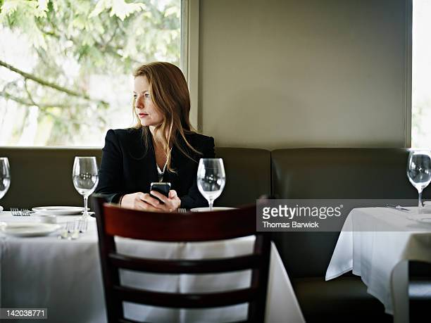 Businesswoman in restaurant looking out window