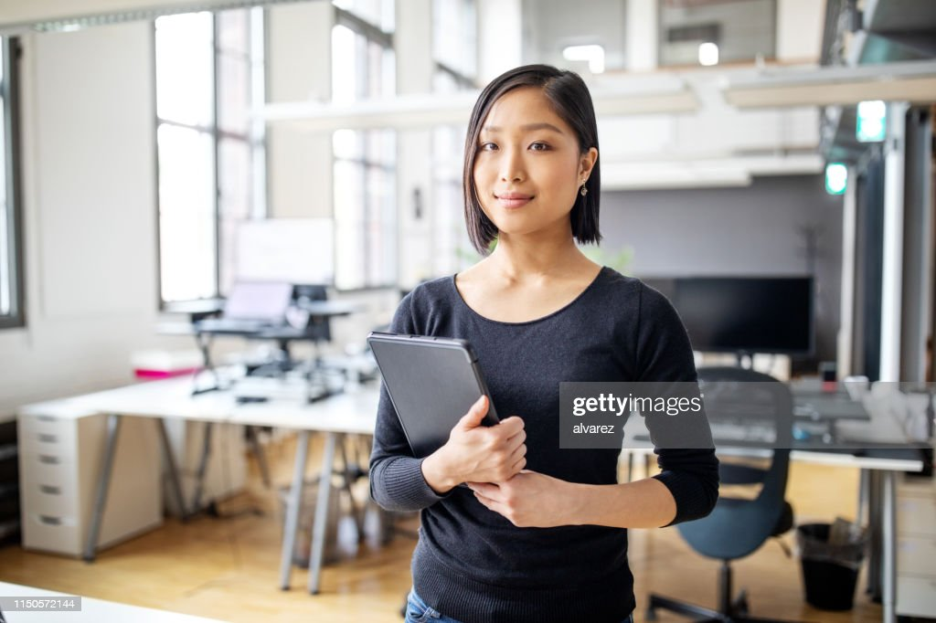 Businesswoman in smart casuals standing in office : Stock Photo