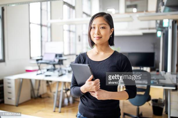 businesswoman in smart casuals standing in office - businesswoman stock pictures, royalty-free photos & images