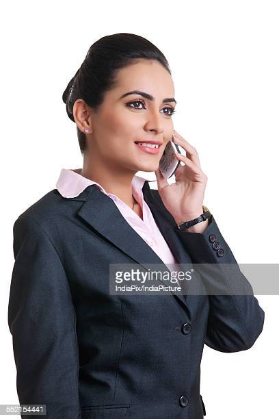 Businesswoman in suit using mobile phone over white background