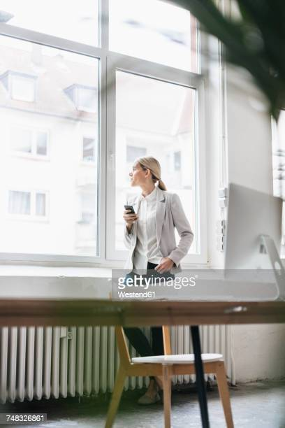 Businesswoman in the office looking out of window