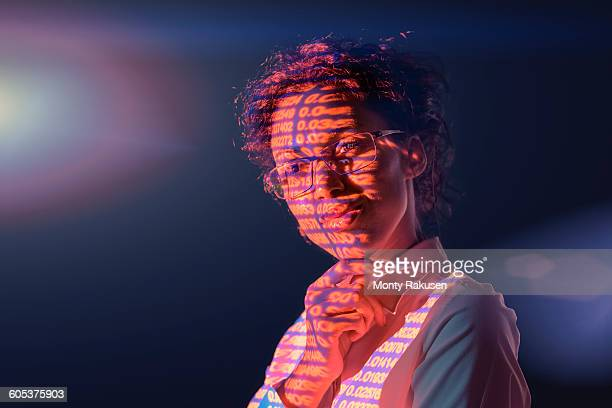 businesswoman in thought with projected financial numbers on dark background - monty rakusen stock pictures, royalty-free photos & images