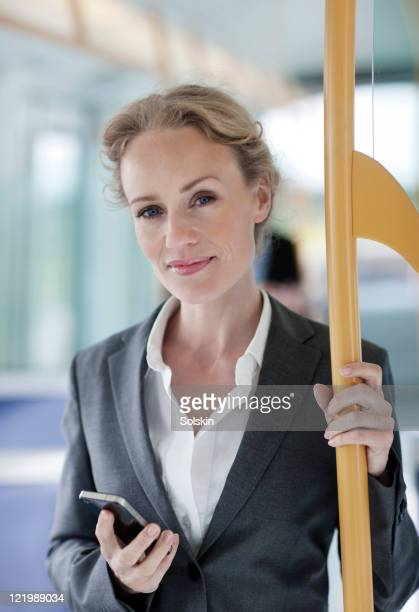 businesswoman in train, holding phone