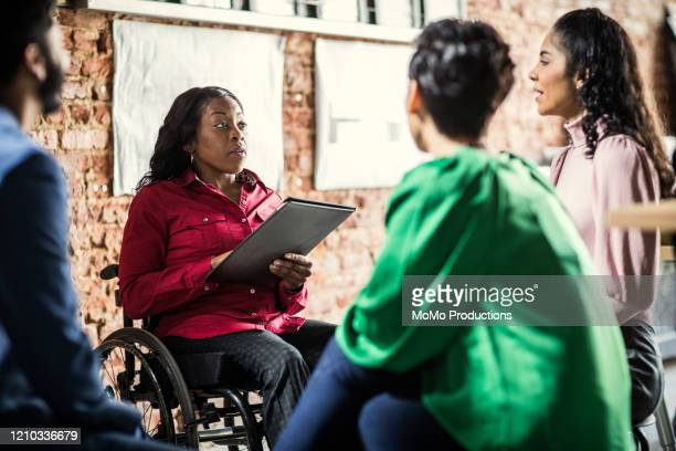 businesswoman in wheelchair leading group discussion in creative office - persons with disabilities stock pictures, royalty-free photos & images
