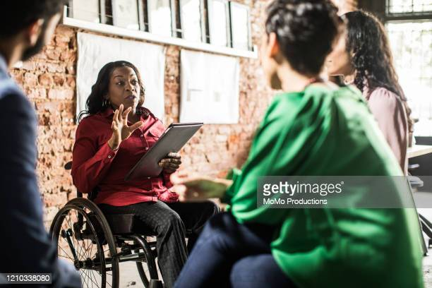 businesswoman in wheelchair leading group discussion in creative office - employee engagement stock pictures, royalty-free photos & images