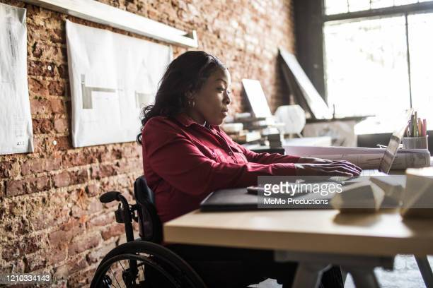 businesswoman in wheelchair working at desk - differing abilities fotografías e imágenes de stock